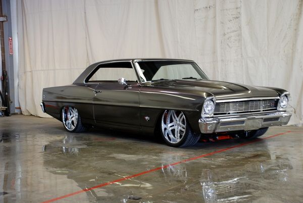 Eighty 1 Design in Mukilteo, Washington built this wild Nova with an air-ride suspension, Chevy 502, custom exhaust, 20″ wheels, and a full custom audio system including navigation. The hood opens forward and the gas tank cap was relocated behind the driver's side tail light. See more pics on their '66 Nova ride page. grey