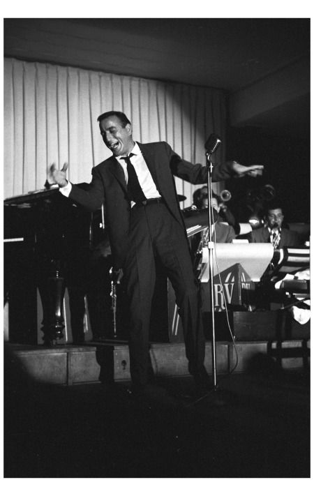 Tony Bennett wearing a dark suit performing at a night club with band