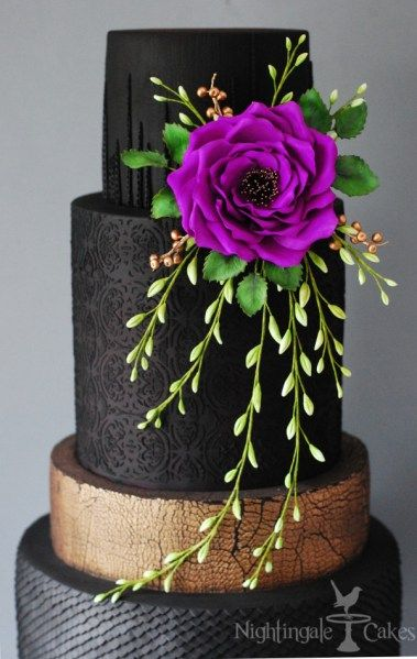 Black wedding cake with purple sugar rose and green foliage and gold details.
