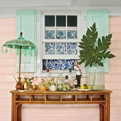 A rattan console Becker found on eBay anchors the porch bar. The table umbrella is Balinese, and the greenery is from a local papaya tree.