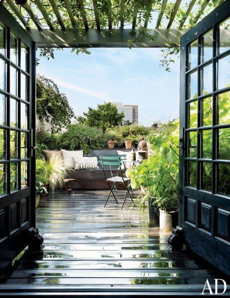 French doors open onto a lush rooftop garden outfitted with bistro chairs by Fermob at hairstylist Guido Palau's artful Manhattan duplex.Pin it.