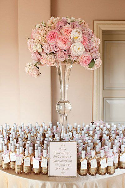 Use escort cards that double as favors, like these mini champagne bottles.Photo Credit: Aaron Delesie / Event Design: Bella Destinee…
