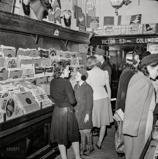 "December 1941. Washington, D.C. ""Christmas shopping in Woolworth's five and ten cent store record department."" Records sold  for 53 cents each"