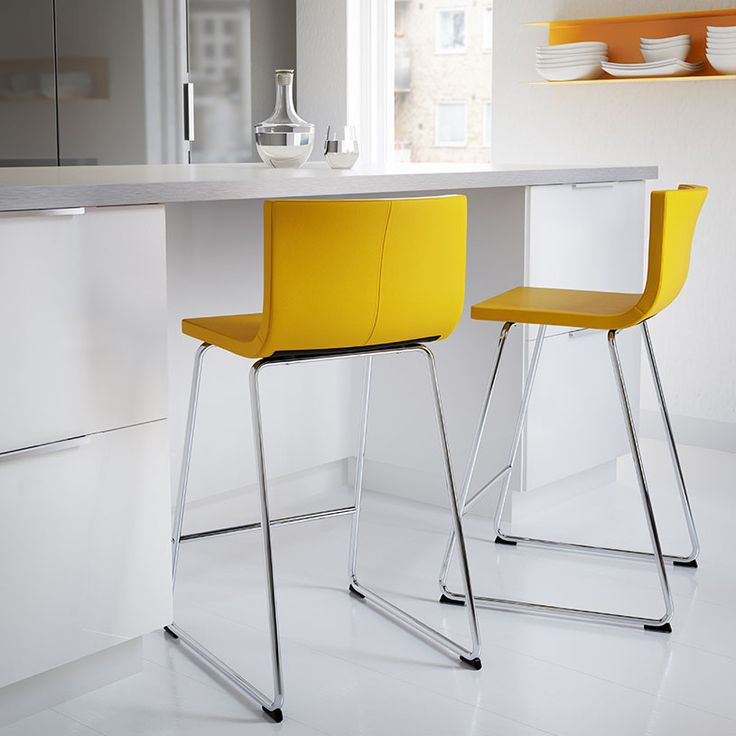 Two bar stools with yellow seat and chrome-plated legs in front of a kitchen island