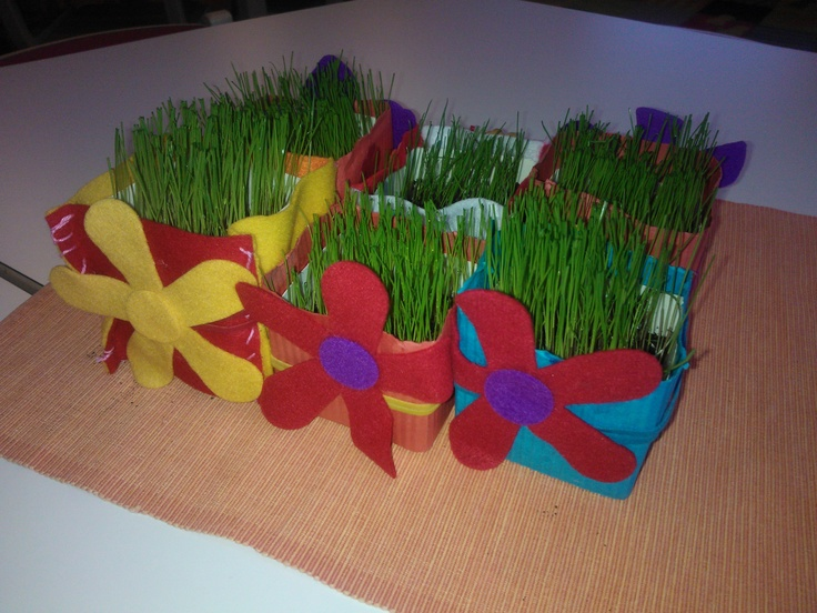 A pot for Easter grass. Felt over milk carton, either sewn or glued. A leatherlike twine wrapped around and felt flowers glued on top.