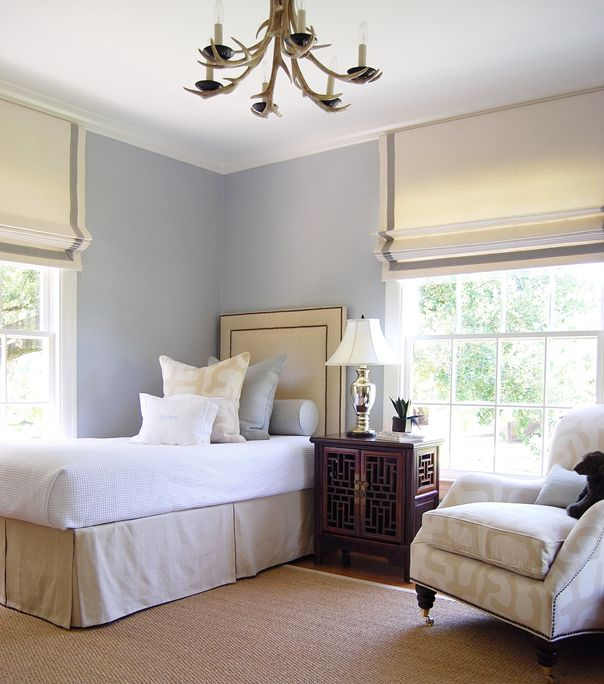 pale blue walls, crisp roman shades, nailhead upholstered headboard, fretwork side table, and an antler ceiling fixture.  Simple and classic.  Ashley Goforth.