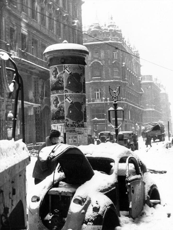 """Autóroncs a Váci utcában, 1945 telén. A hirdetőoszlopon a szokásos programajánlók mellett két """"helytállunk"""" feliratú propagandaplakát."""