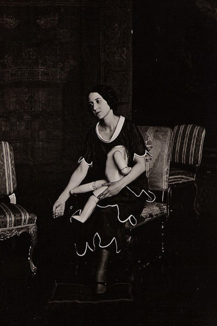 Portrait de Lise Deharme avec une poupée cassée vers 1930.  Lise Deharme (1898 _ 1980) romancière et poétesse française et l'une des muses du surréalisme.  Elle rencontre André Breton en octobre 1924. Il lui demande de laisser l'un de ses gants de daim bleu pâle comme symbole du mouvement surréaliste. L'épisode est relaté par Breton dans son récit Nadja où Lise Deharme apparaît sous le nom de Lise Meyer.