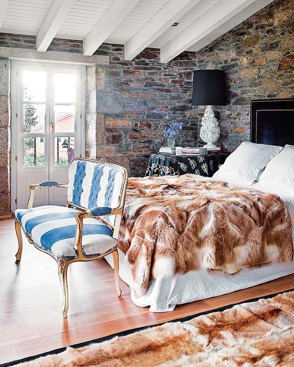 Precioso dormitorio con banqueta tapizada a rayas y techo de piedra