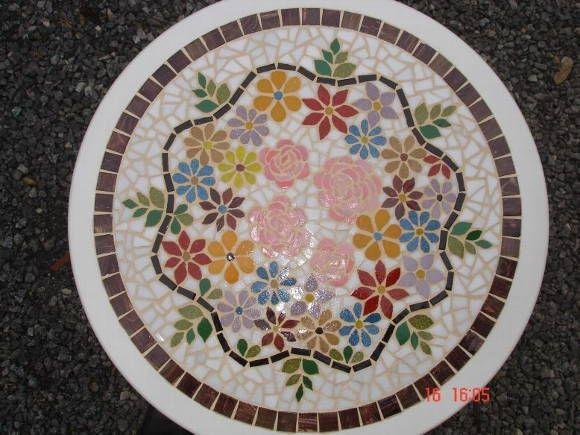 Tampo de mesa feito em mosaico de pastilhas de vidro, motivo floral. R$ 648,00