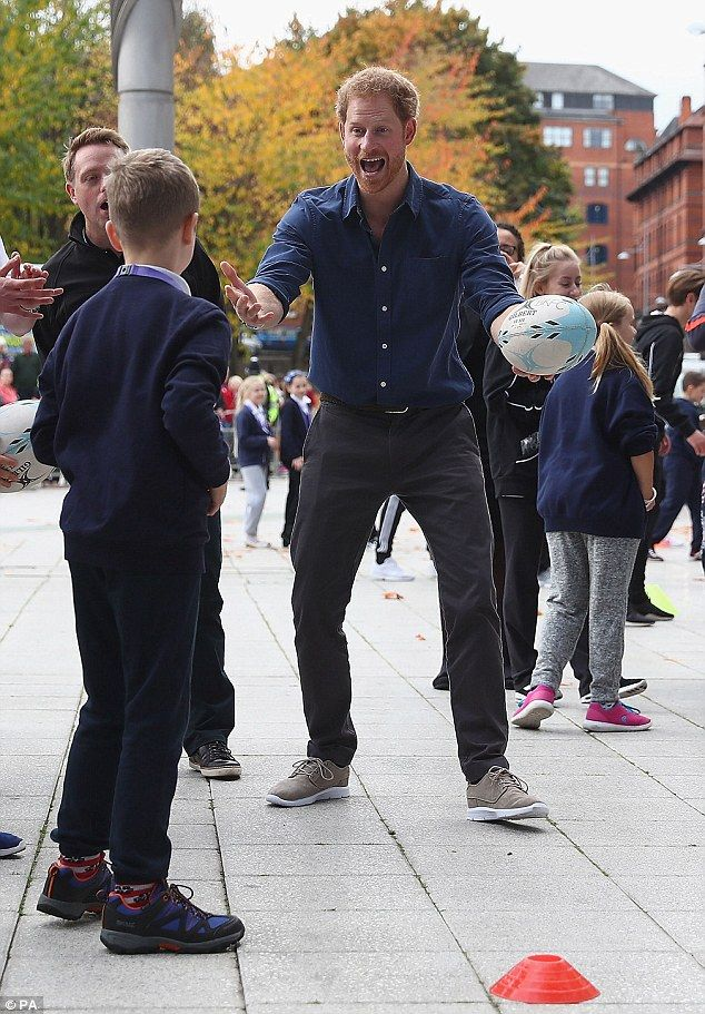 Sporty Harry looked in typically high spirits as he gestured to a young rugby fan during a...