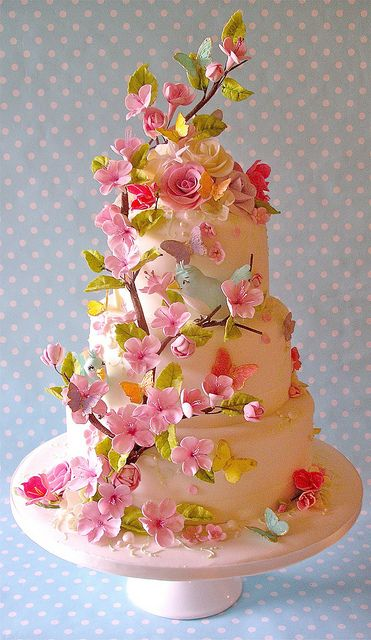 cake abundant with branches of blossoms and icing flowers