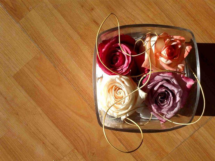 Diseño floral de rosas ecuatorianas sobre piedras en florero cubo.