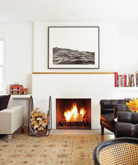 The design of this living room is simple and streamlined, yet there's a nod to cosiness. A horizontal  piece of wood delineates the fireplace mantel and echoes the horizontal lines of the shelving