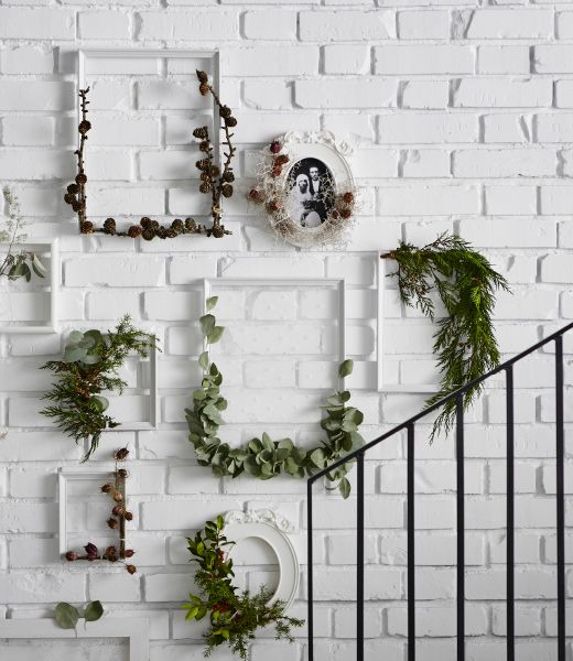 IKEA KNOPPÄNG frames are hung on a white brick wall and wound partially with greenery for a holiday decoration.