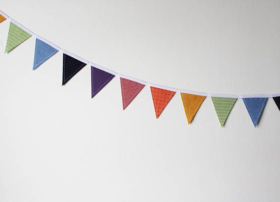 """Rainbow Mini Fabric Bunting. Fabric bunting can be used over and over again! Party decorations, nursery or kid's room decor, over a doorway or around a window, the options are endless!   These bunting strands each have 18 double-sided flags measuring 3"""" by 3.5"""". The total length of each bunting strand is about 6 feet. The bunting has been treated with a spray starch alternative, and can be ironed as needed. #theevergreencollective"""