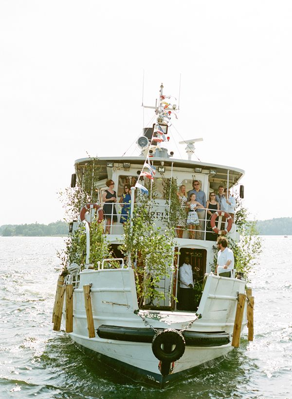 Wedding guests were ferried from Stockholm on a Swedish tour boat decked in flowers! Photo: Nina & Wes | Snippet & Ink