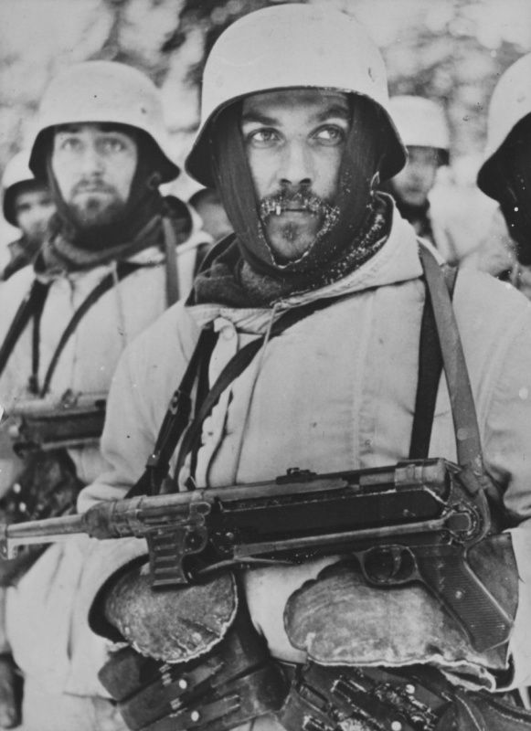 German soldiers in winter uniform in service on the Eastern Front. The soldier in the foreground is armed 9mm submachine gun MP-40.