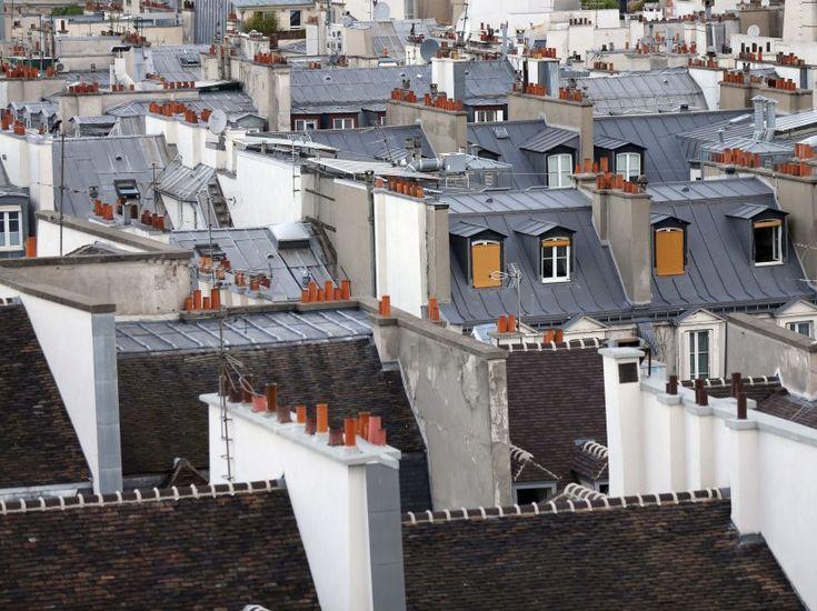"""Toits d'immeubles à Paris sur une photo prise en juin 2013. """"Au 7e étage de Paris, nous pouvons observer un panel de couleurs : les tuiles rouges, les ardoises – gris-bleu – le cuivre devenu vert, et le zinc gris pâle, sans oublier l'or sur les Invalides, par exemple"""", a encore indiqué la maire du 9e arrondissement. (AFP PHOTO/THOMAS SAMSON)"""