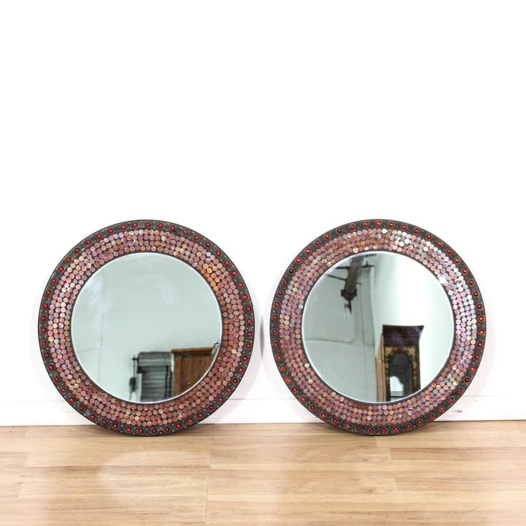 This pair of mirrors are featured in a wood with a black distressed finish. These accent mirrors have round circle frames, shiny red mosaic tile and brass beaded stud trim. Eclectic mirrors perfect for a bohemian space! #americantraditional #decor #mirror #sandiegovintage #vintagefurniture