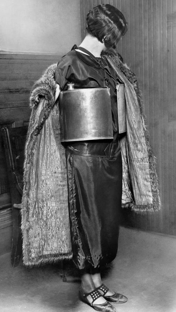 "A bootlegger arrested by the Minneapolis police displays her apparatus for dispensing ""wet goods"" during prohibition. April 10, 1924. The term ""bootlegging"" was popularized when thousands of city dwellers would sell liquor from flasks they kept in their boot leg all across major cities."