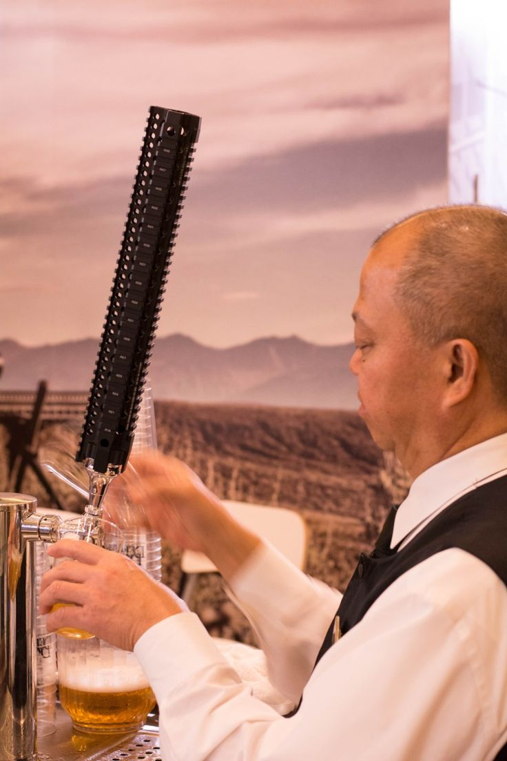 SHOT Show 2016 Recap – Group. A bartender pours beer from a quad rail tap at the Daniel Defense booth.