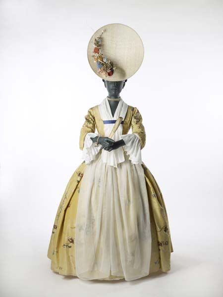 "1743-1750 ""The dress is made of yellow silk taffeta, which is brocaded. This means that the flower design is not embroidered, but woven into the fabric. The skirt of this gown is attached to the bodice at the back and side, the front part of the skirt is held up by strings tied around the waist."""
