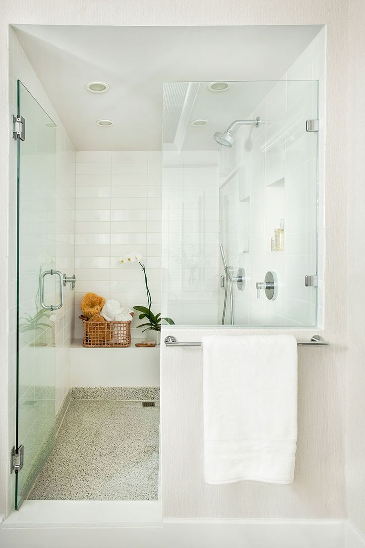 Luxurious white shower with frameless glass door