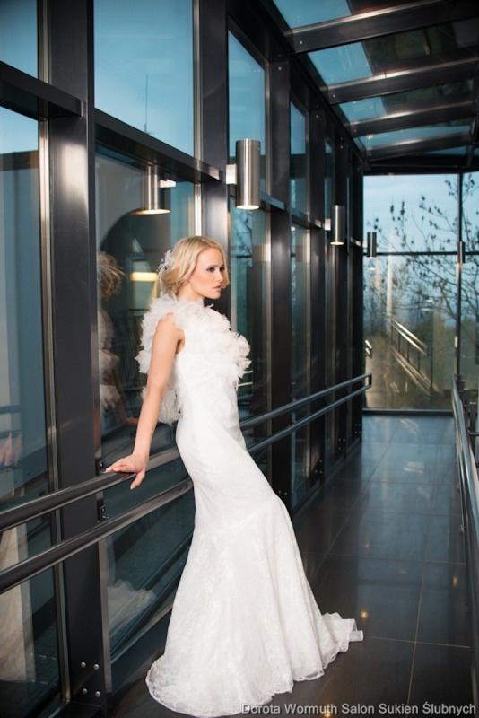 Koronkowa suknia z asymetryczną ozdobą na ramieniu.