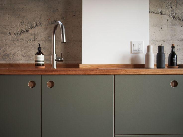 Basis Linoleum in der Farbe 'Olive' mit Griffen aus Natureiche. Die Arbeitsplatte ist Eiche massiv.