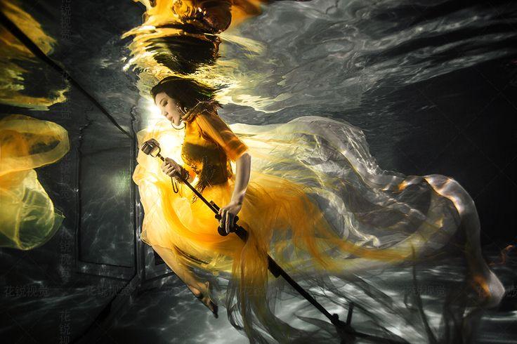 Girl in yellow dress underwater.