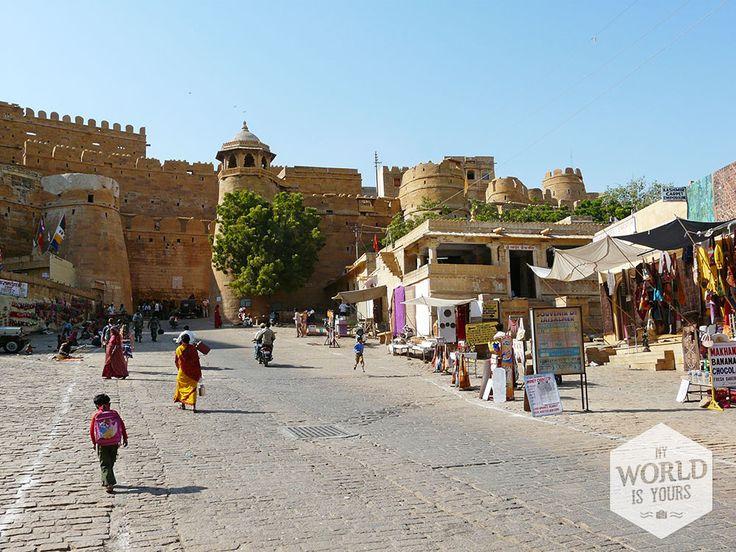 Als je erboven zou vliegen op een magisch tapijt, dan zou je de stad misschien niet eens zien liggen. De lichtgele stenen van de huizen in Jaisalmer gaan moeiteloos over in het dorre landschap van de woestijn. Maar wrijf dat zand eens uit je ogen, zie je daar dan niet dat grote zandkasteel? #Jaisalmer #fort #India #Rajasthan