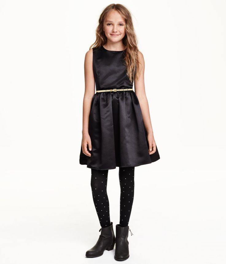 Ærmeløs kjole i vævet kvalitet. Er skåret i taljen og har underdel med vidde. Synlig lynlås i ryggen. Er foret foroven. Medfølgende bælte i imiteret laklæder.