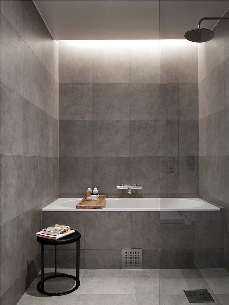 paired back grey bathroom with recessed light designed to wash the wall