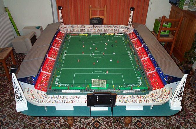 Simple Subbuteo stadium with Red & White grandstands, and grey terracing.