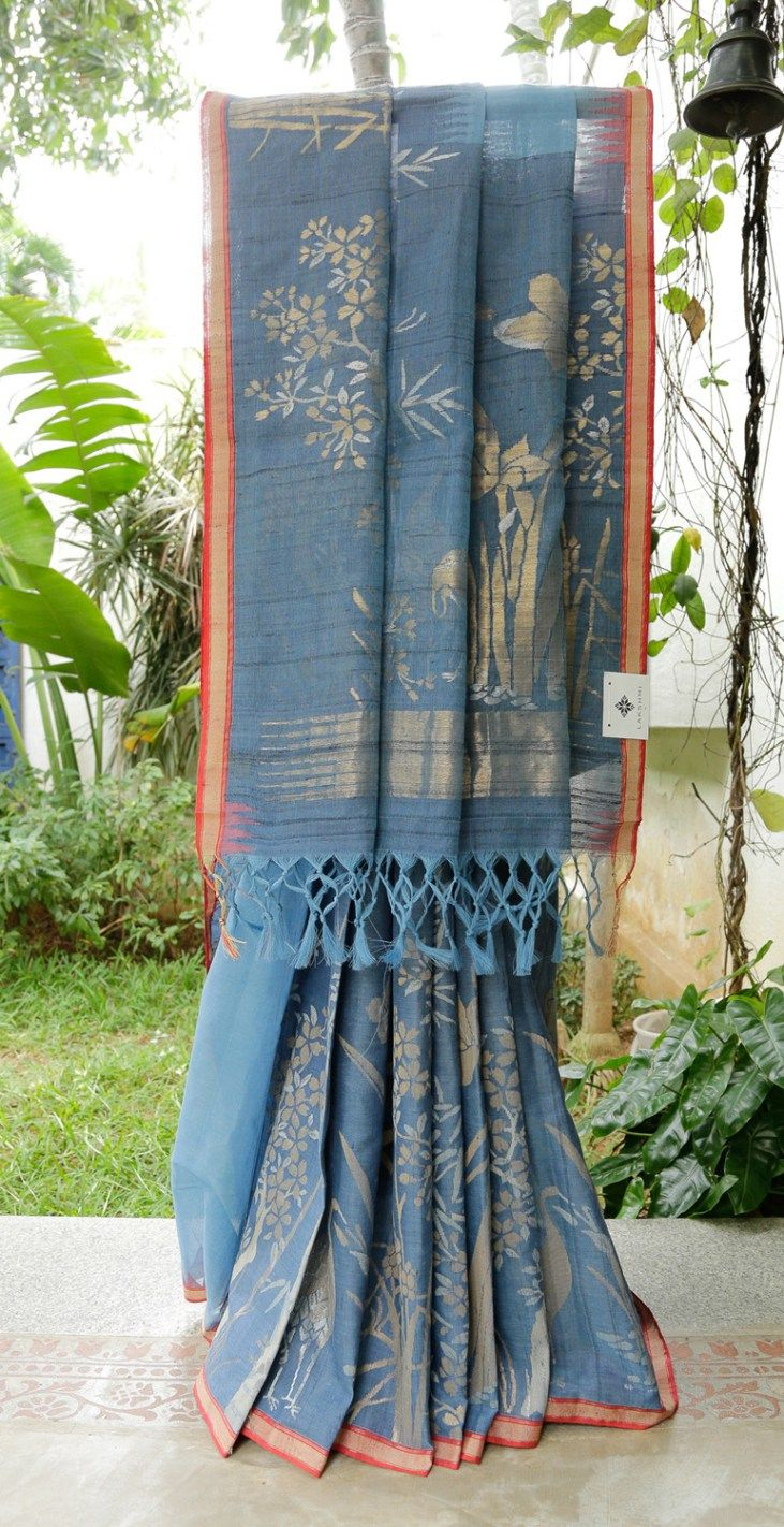 This khadi sari is in Aegean blue with jamdani work in silver and gold zari. The border is in sangria red, gold zari and oat tan and the pallu is in Aegean blue with silver and gold zari giving it …