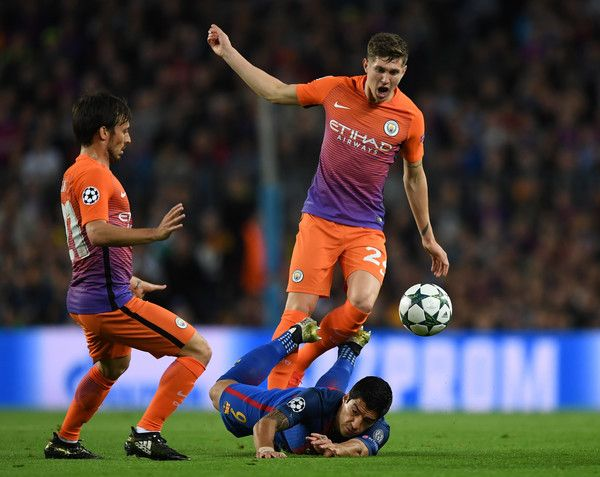 Luis Suarez of Barcelona goes down under the challenge of John Stones of Manchester City during the UEFA Champions League group C match between FC Barcelona and Manchester City FC at Camp Nou on October 19, 2016 in Barcelona, Catalonia.