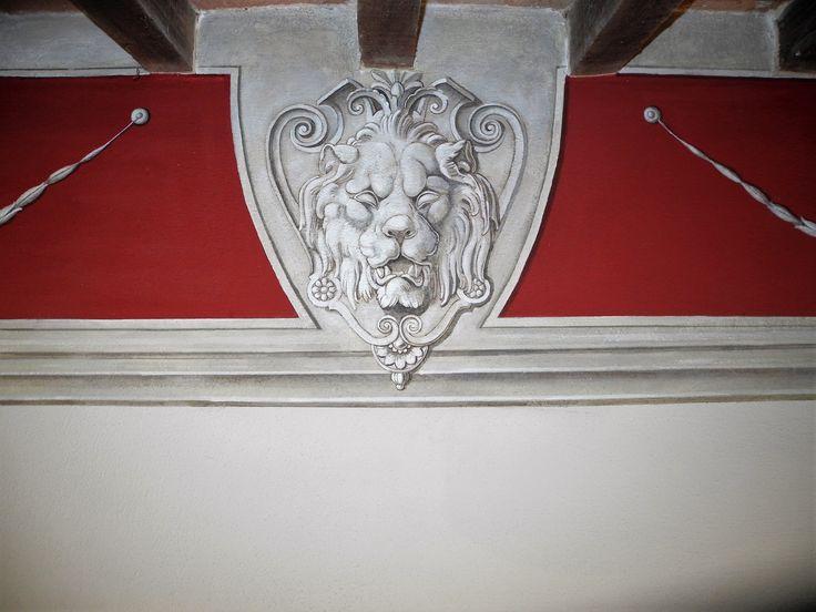 Fascia perimetrale alta dipinta con tempera acrilica Testa leonina realizzata con tecnica grisaille