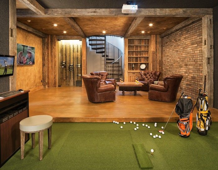 Keller ausbauen Spielraum Erholungsbereich einrichten eingebaute Beleuchtung Ohrensessel Leder Holz grüner Bodenbelag sehr ansprechend