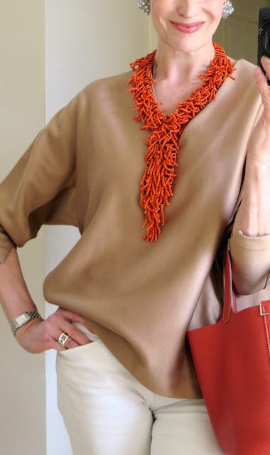 Fantastic style. Love the rich burnt orange necklace and bag against the neutral camel and off-white.