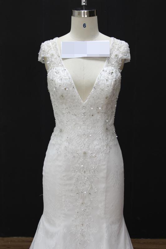 Vestido de noiva semi sereia, decote em V, corpete bordado em pedrarias, transparência nas costas. Via Brasil Noivas.