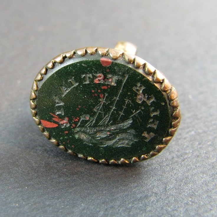 """Bloodstone Wax Intaglio Seal/Fob: """"A teeny little wax seal from the 1830's period in England. Highly ornate bexel, shoulders and suspension loop. Made from a brass metal which was once gilded. The tiny flower decorations and scrolling are divine. The matrix is carved from bloodstone and has a masted sailing ship run aground on rocks. The motto around the matrix is in French stating 'Telle Est La Vie' or 'Such Is Life.'"""""""