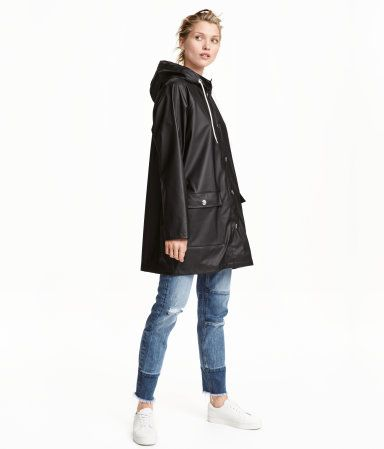 Black. Raincoat in water-repellent functional fabric with welded seams. Drawstring hood, snap fasteners at front, and front pockets with flap. Unlined.