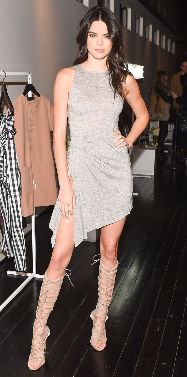 Kendall Jenner celebrated the launch of her new clothing line Kendall + Kylie in one of her own designs—a gray ruched T-shirt dress with killer nude knee-high lace-up heels.