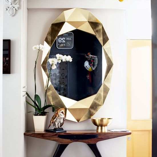 Love this! Add drama to a small space by setting a large gold mirror against a plain white backdrop to create a grand entrance.