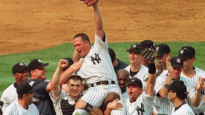 """David Cone is lifted onto the shoulders of his teammates by catcher Joe Girardi (second from left) and second baseman Chuck Knoblauch (second from right) to celebrate a perfect game against the Montreal Expos during """"Yogi Berra Day"""" on July 18, 1999, at Yankee Stadium"""