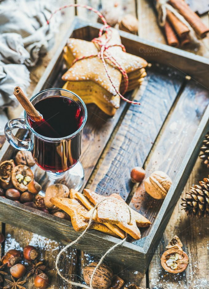 #Glass of mulled wine  Glass of mulled wine in wooden tray with Christmas gingerbread cookies nuts cinnamon anise and pine cones over rustic wooden background selective focus copy space vertical composition