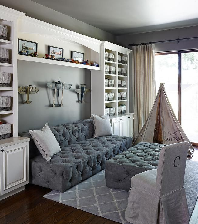 Contemporary family room features a gray painted ceiling over gray walls lined with a collection of vintage airplanes over a gray tufted armless sofa and ottoman, Restoration Hardware Soho Upholstered Armless Sofa with Soho Upholstered Coffee Ottoman, flanked by built-in shelves stacked atop built-in cabinets.