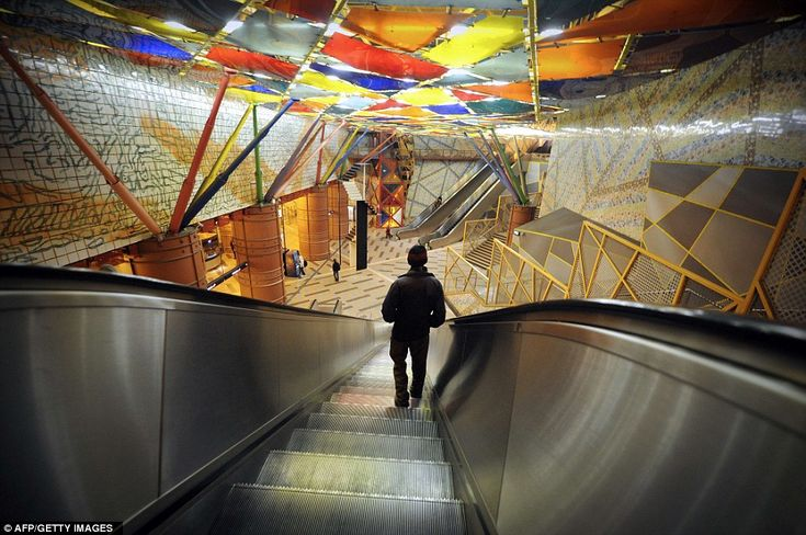 Colourful: A subway passenger stands on an escalator at the Olaias metro station in Lisbon