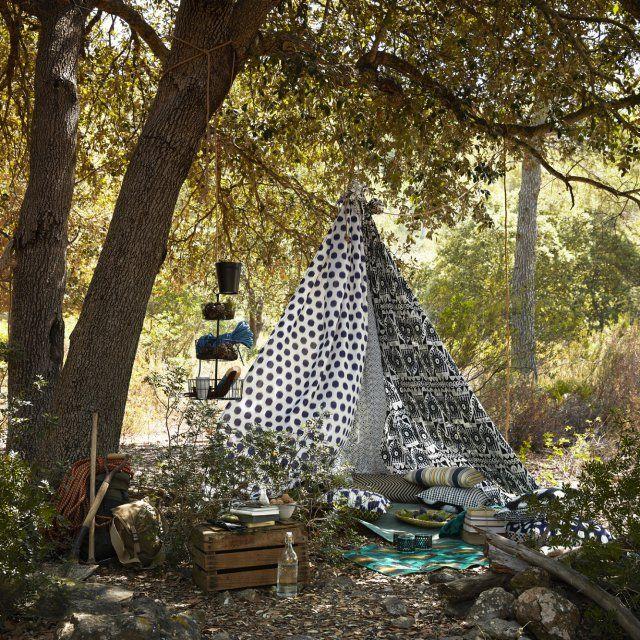 On fabrique une tente bohème dans le jardin grâce à des rideaux IKEA aux motifs noirs et blancs et on installe quelques coussins à l'intérieur.